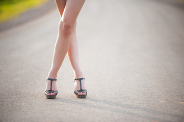 beautiful woman legs in high heel shoes on the road