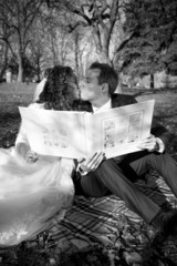 Monochrome portrait of just married couple holding photo album