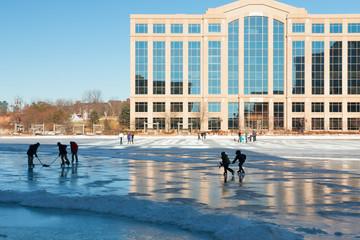 Kids play hockey on a frozen lake