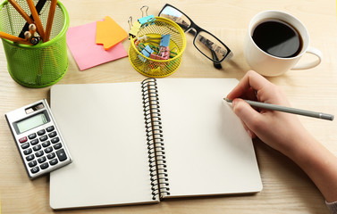 Female hand writing at notebook with cup of coffee at wooden