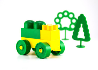 Colorful plastic toy blocks car and trees.