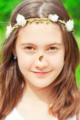 Summer surprise. Girl with floral headband on head and butterfly