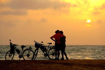 夕日を見ながら、キスするカップル