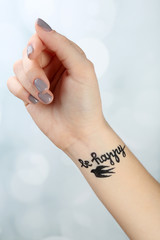 Female arm with tattoo on light background