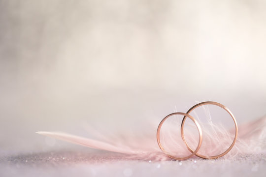 Two Golden Wedding Rings and  Feather - gentle background