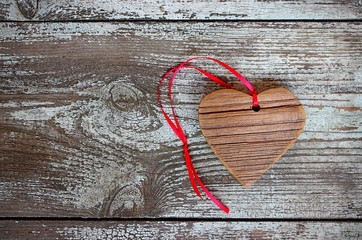 Wooden heart with red ribbon on a wooden table