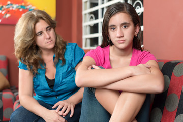 Worried and sad mother looks at her defiant teen daughter