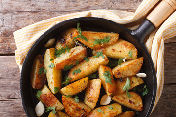 potatoes fried in a pan, horizontal top view closeup, rustic