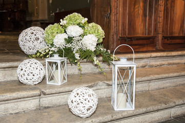white lanterns on the pavement and flowers