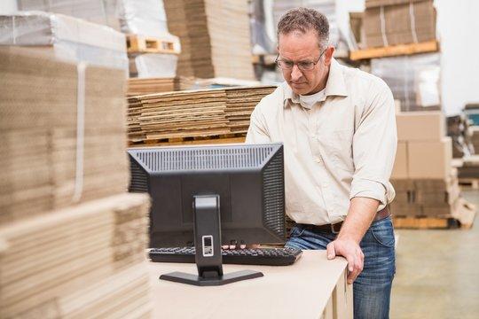 Serious warehouse worker using laptop
