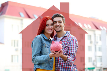 Loving couple with piggy bank near apartment house