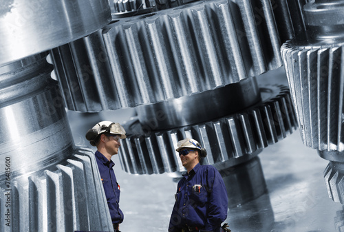 Wall mural engineers, workers with cogwheels and gear machinery