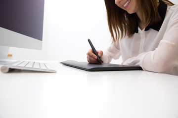 Closeup image  of female hands working on graphic tablet