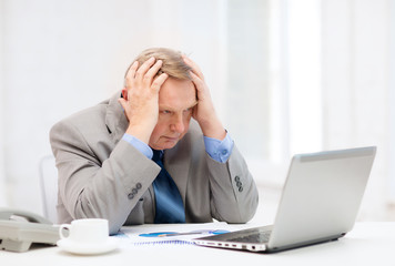 upset older businessman with laptop and telephone
