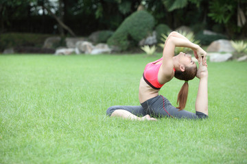 Young cute woman in the Pigeon yoga pose on lawn