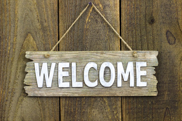 Wood welcome sign hanging on rustic wooden background