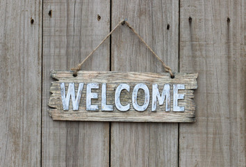 Wood welcome sign hanging on wooden fence