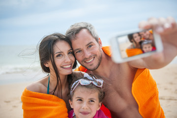 A young couple and their daughter taking a selfie