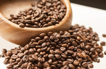 Heap of Brown Roasted Coffee Beans in Wooden Bowl on White Surfa