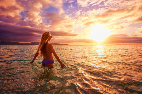 Carefree woman in the sunset on the beach. vacation vitality hea