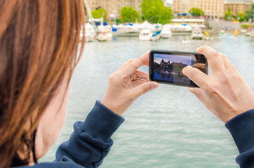 Woman Taking Photos with a Mobile Phone from a Ship in Harbour