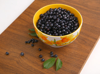 blueberries with leaf in bowl, cup, plate on wooden background
