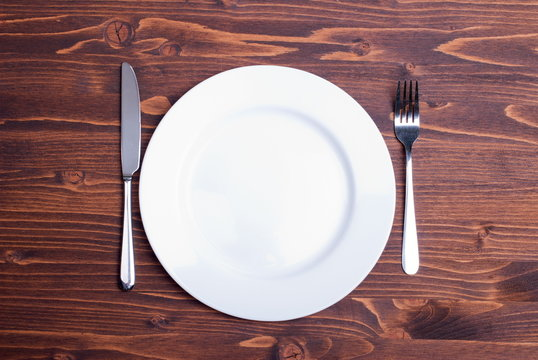 white plate and fork next to a knife on a wooden board top view
