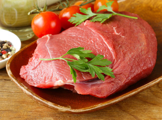fresh raw beef meat with pepper and herbs on wooden plate