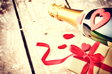 Valentine's setting with present and bottle of champagne