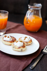 Delicious homemade cheese pancakes with fresh carrot juice