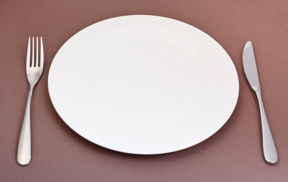 white porcelain plate with fork and knife on brown