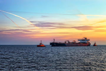 Tanker ship with escorting tugs on sea at sunrise.