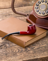 tobacco pipe old telephone and book on wooden palette