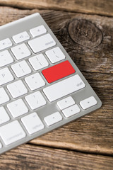 Blank empty red button on the keyboard close-up on wooden backgr