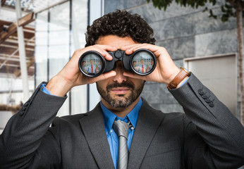 Businessman using binoculars, people portraits in the lens