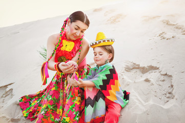 Toned photo of happy Mom and son dressed in Mexican clothes play