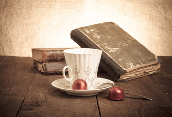 Cup of coffee, shokolad and stack of old books on the old wooden