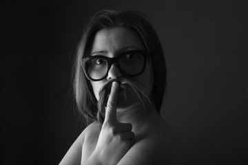 Woman imitating a man with moustaches and eyeglasses
