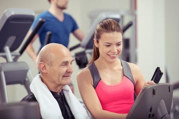 trainerin im fitness-studio berät einen älteren kunden