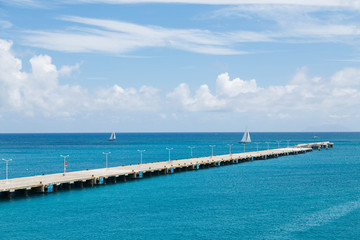 Two White Sailboats Beyond Long Concrete Pier