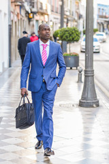Black businessman walking on the street with a modern briefcase
