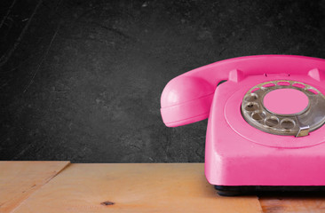 Retro pink telephone on wooden table and blackboard Background