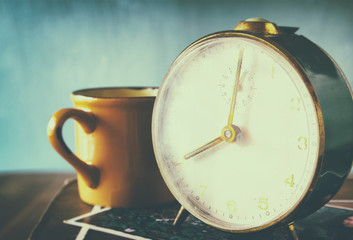 close up image of old clock and cofee cup over wooden table. ima