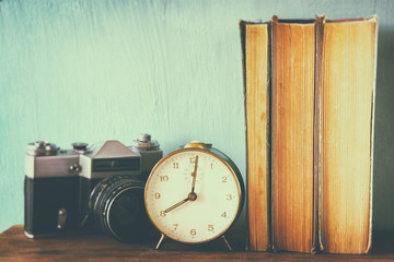 stack of books, old clock and vintage camera over wooden table.