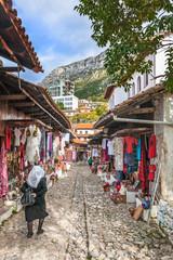 Elderly woman walking along the bazaar ok Kruja