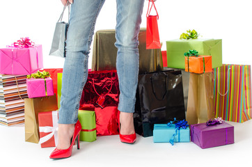 Woman standing before many gifts and shopping bags