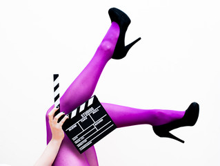 Female legs in pink pantyhose and black high heels with movie cl