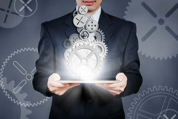 businessman holding tablet showing gears, business strategy conc