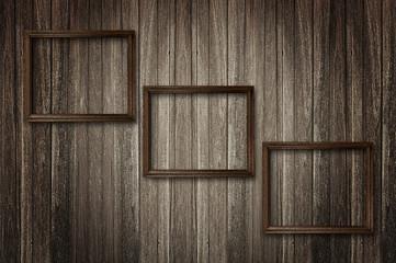 Photo frames on dark wooden wall