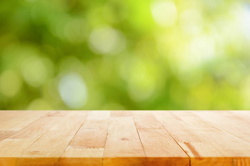 Wood table top on bokeh abstract nature green background